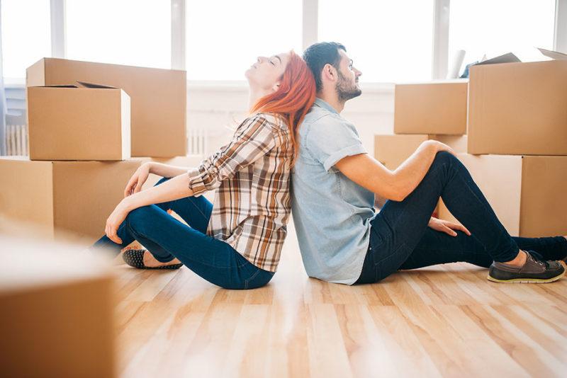 Nuori nainen ja mies istumassa helpottuneina lattialla muuttolaatikoiden keskellä