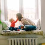 Äiti istumassa ikkunasyvennyksessä pienen lapsensa kanssa