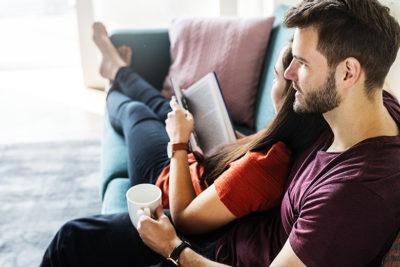 Nuori pari rentoutumassa kotonaan sohvalla