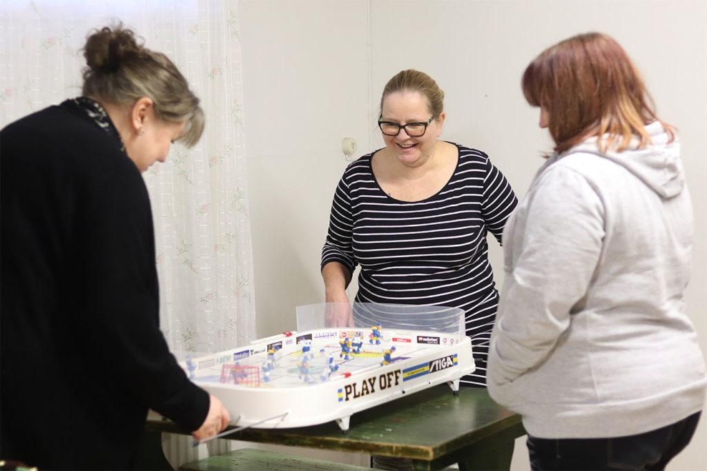 Taru Kockberg, Anri Kamppinen ja Niina Ekman pelaamassa pöytälätkää taloyhtiön kerhotilassa