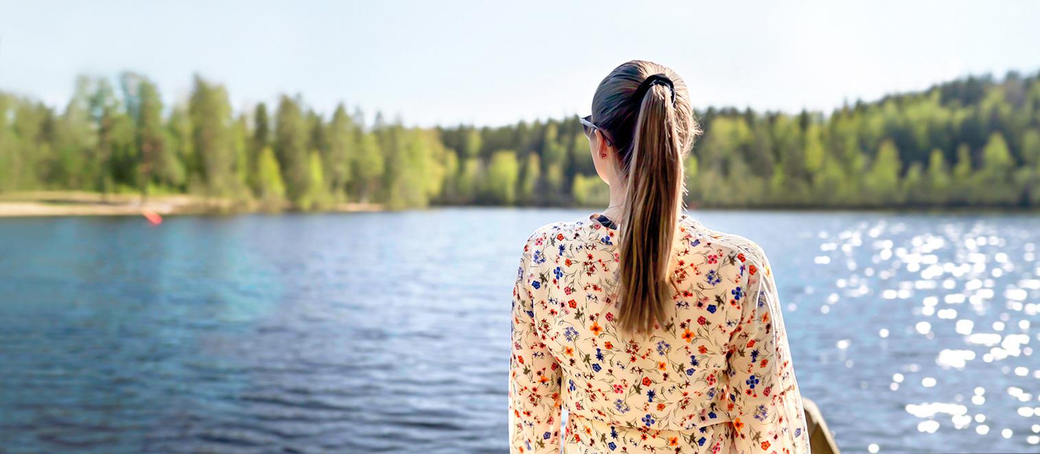Nuori nainen ihastelemassa kesäistä järvinäkymää